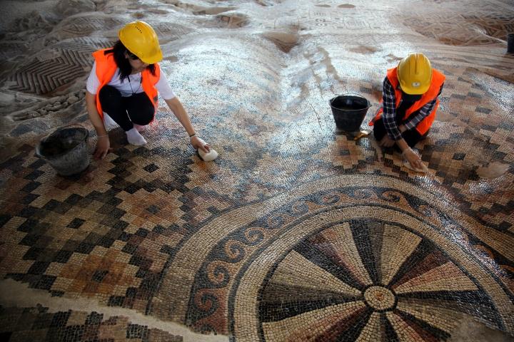 """Hatay'da 2010 yılında bir otelin inşaat çalışması sırasında bulunan, geometrik figür çeşitliliğiyle dikkati çeken bin 200 metrekarelik tek parça taban mozaiği bu yıl içerisinde ziyaretçileriyle buluşacak. MS 6. yüzyıla ait olduğu ve """"kamu alanı"""" olarak kullanıldığı düşünülen eserin """"dünyanın en büyük tek parça taban mozaiği"""" olduğu değerlendiriliyor.  Gün yüzüne çıkarılması için arkeologların büyük bir titizlikle çalıştığı eser, el dokuma kilimi andıran görüntüsüyle de dikkatleri çekiyor. ( Lale Köklü - Anadolu Ajansı )"""